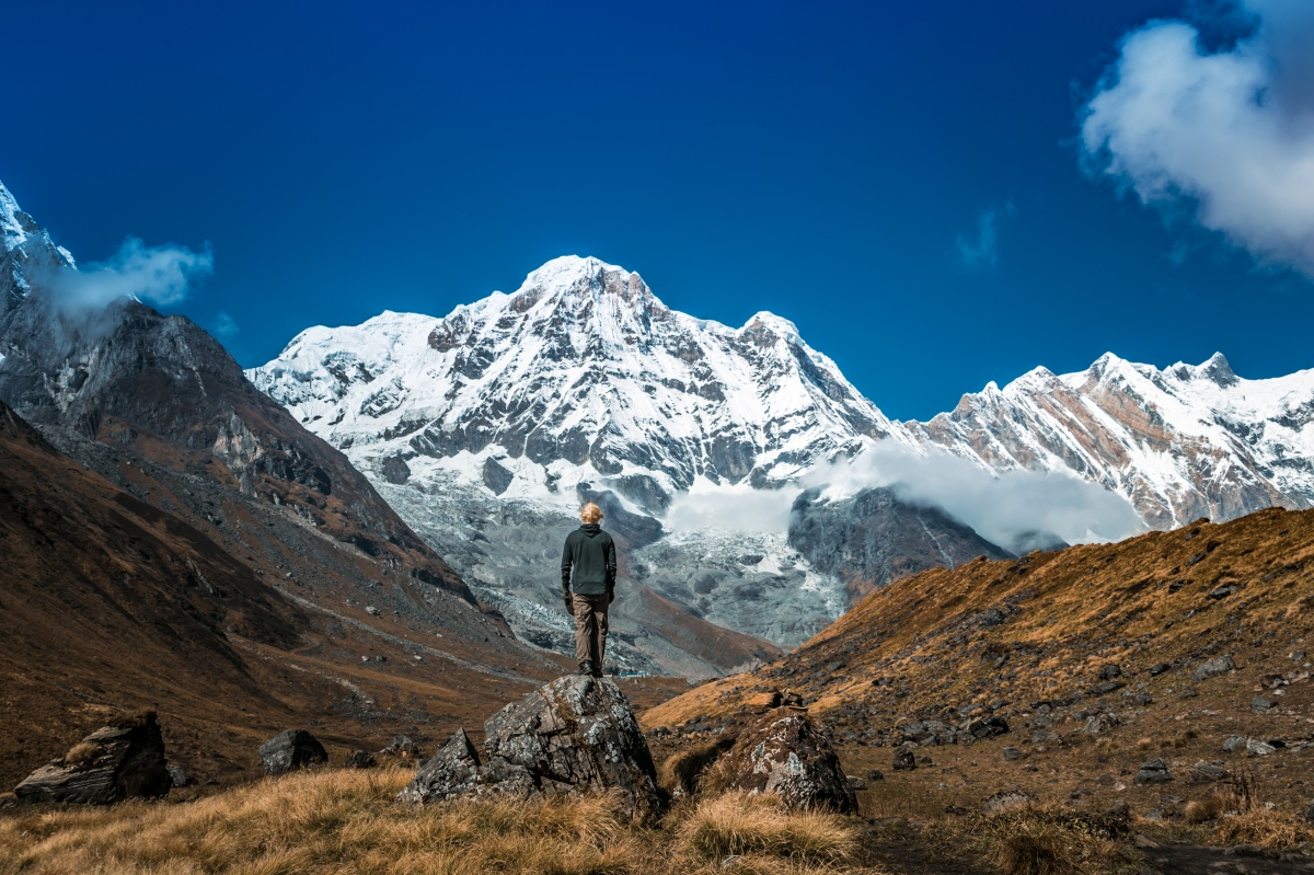 Photo of a man looking in awe at Annapurna mountain range near Annapurna Basecamp in Nepal