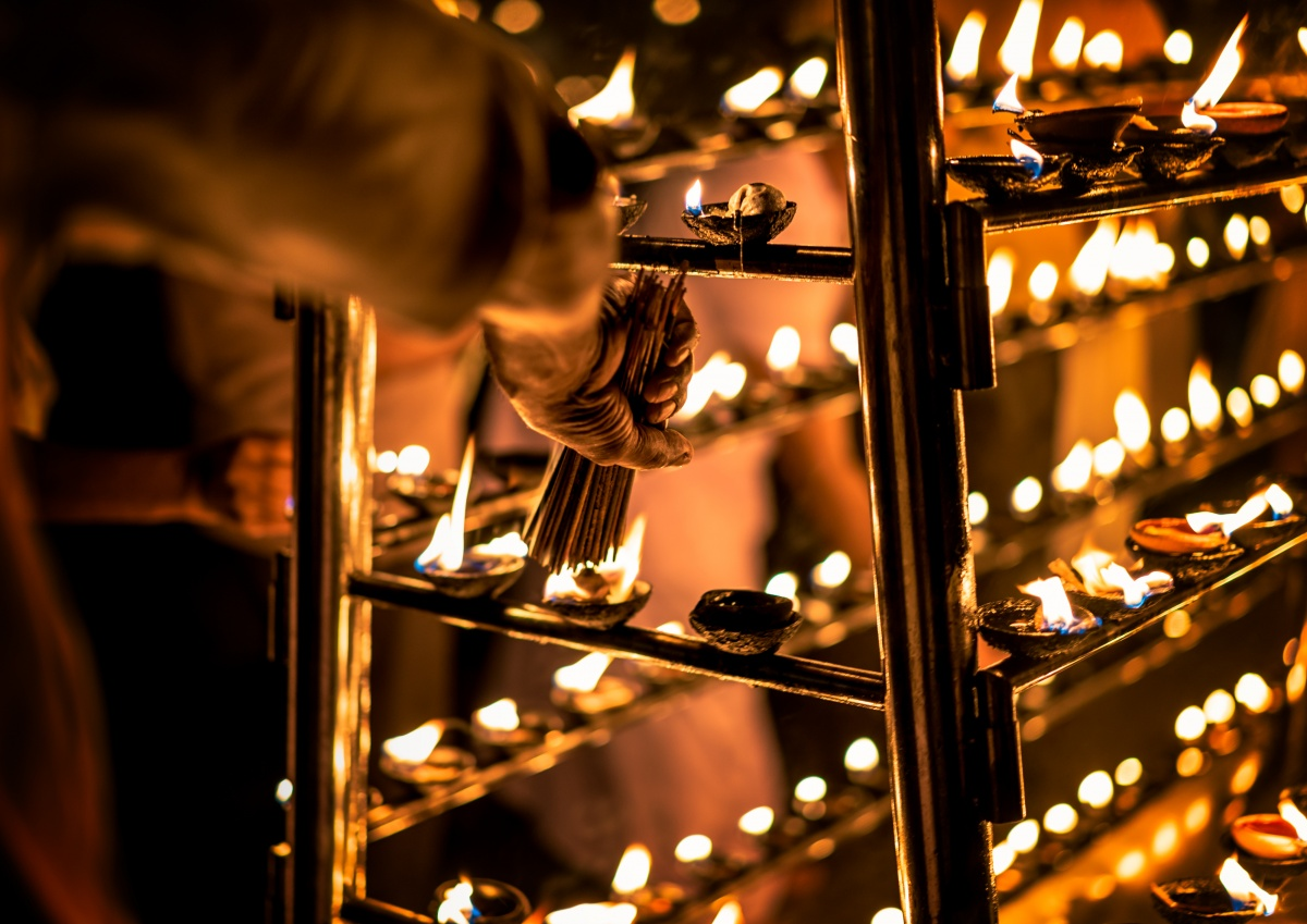 Photo of hundreds of candles and an old man lighting up incense