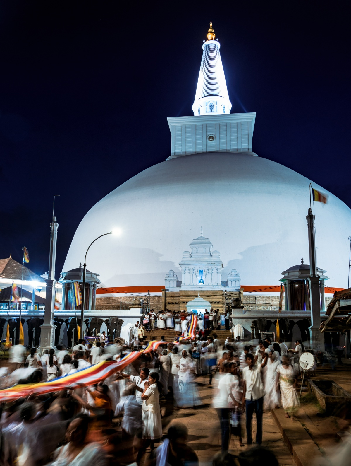 Photo of white stupa in nighttime with people celebrating fullmoon ceremonies carrying hundreds of meters long linen towards the temple to honour Buddha.