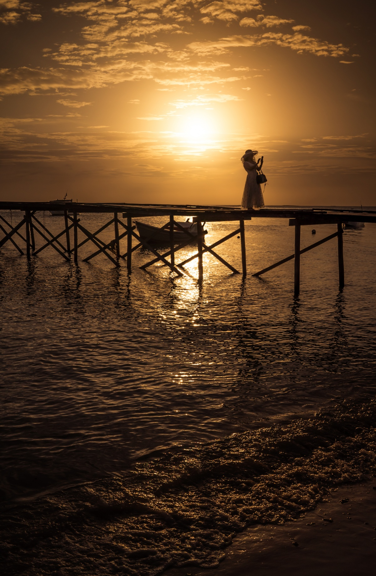 Photo of sunset over pier while picturisque lady is taking a selfie