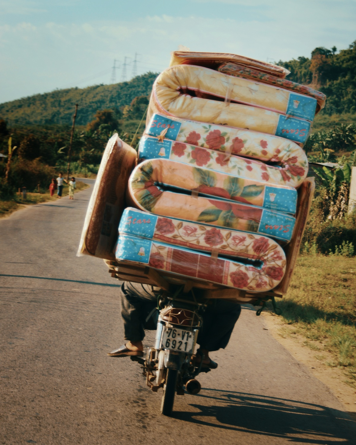 Photo of motorbike guy delivering mattresses and almost falling over