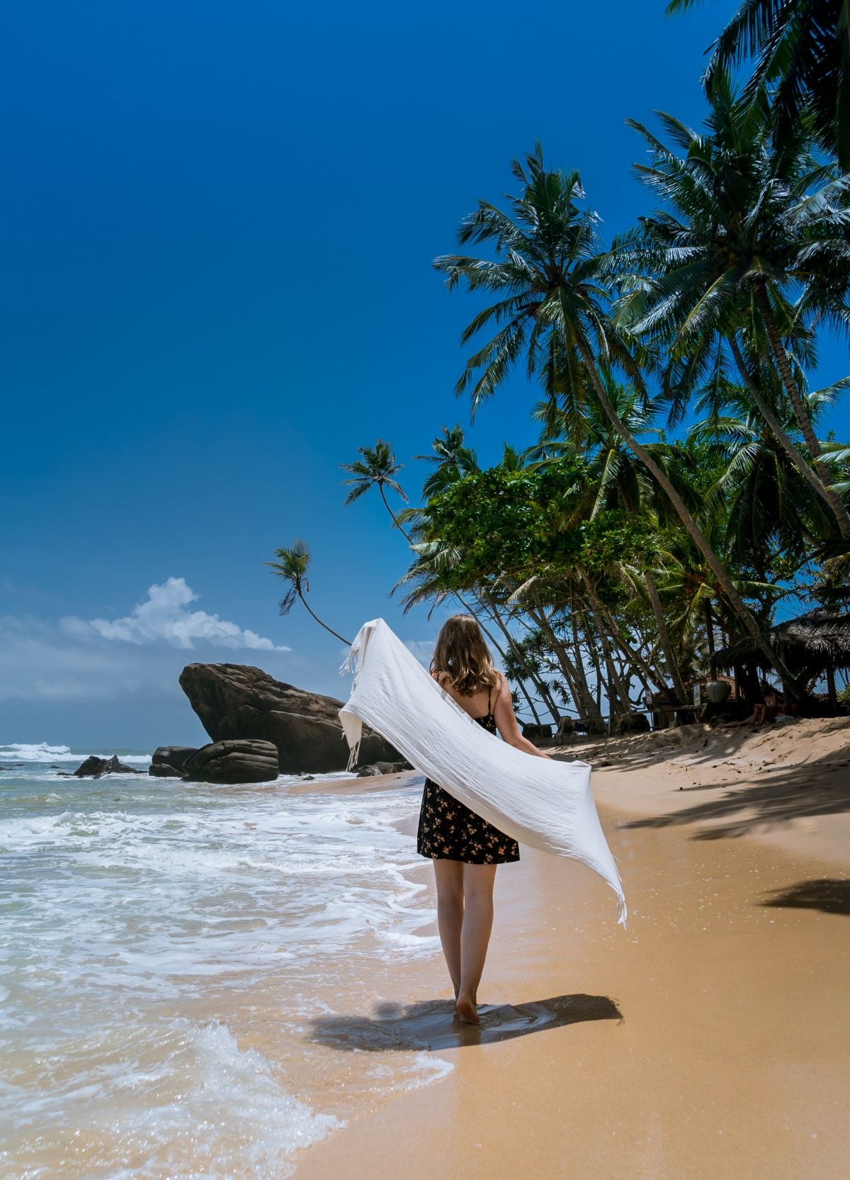 Photo of a woman holding a scarf standing on a beautiful beach in Sri Lanka