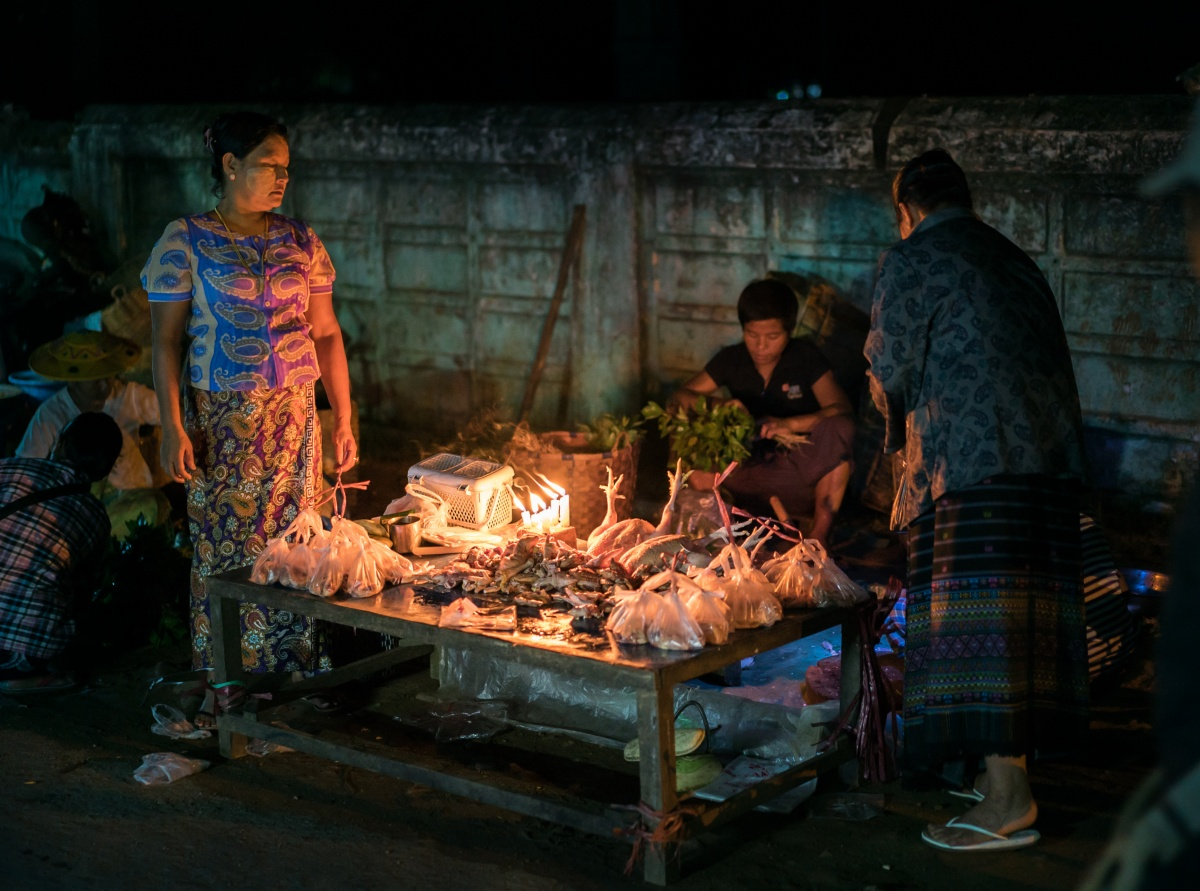 Photo of candle light marketplace table full of chicken. There are three women around the table.