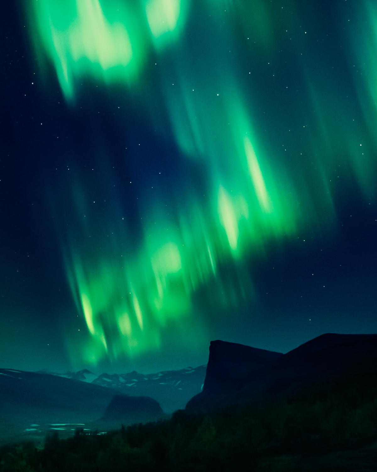 Photo of northern lights over starlit landscape