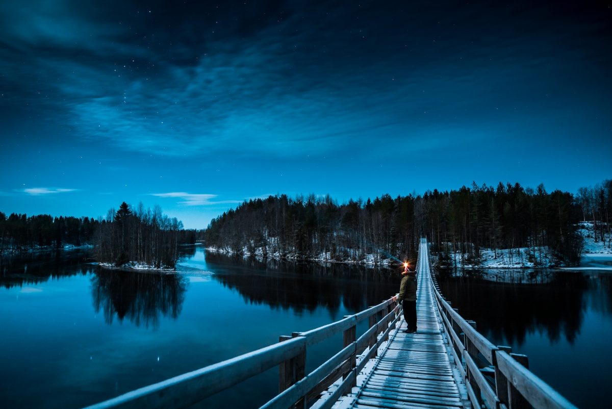 Night view with stars over suspension bridge over frozen river Oulujoki in Finland