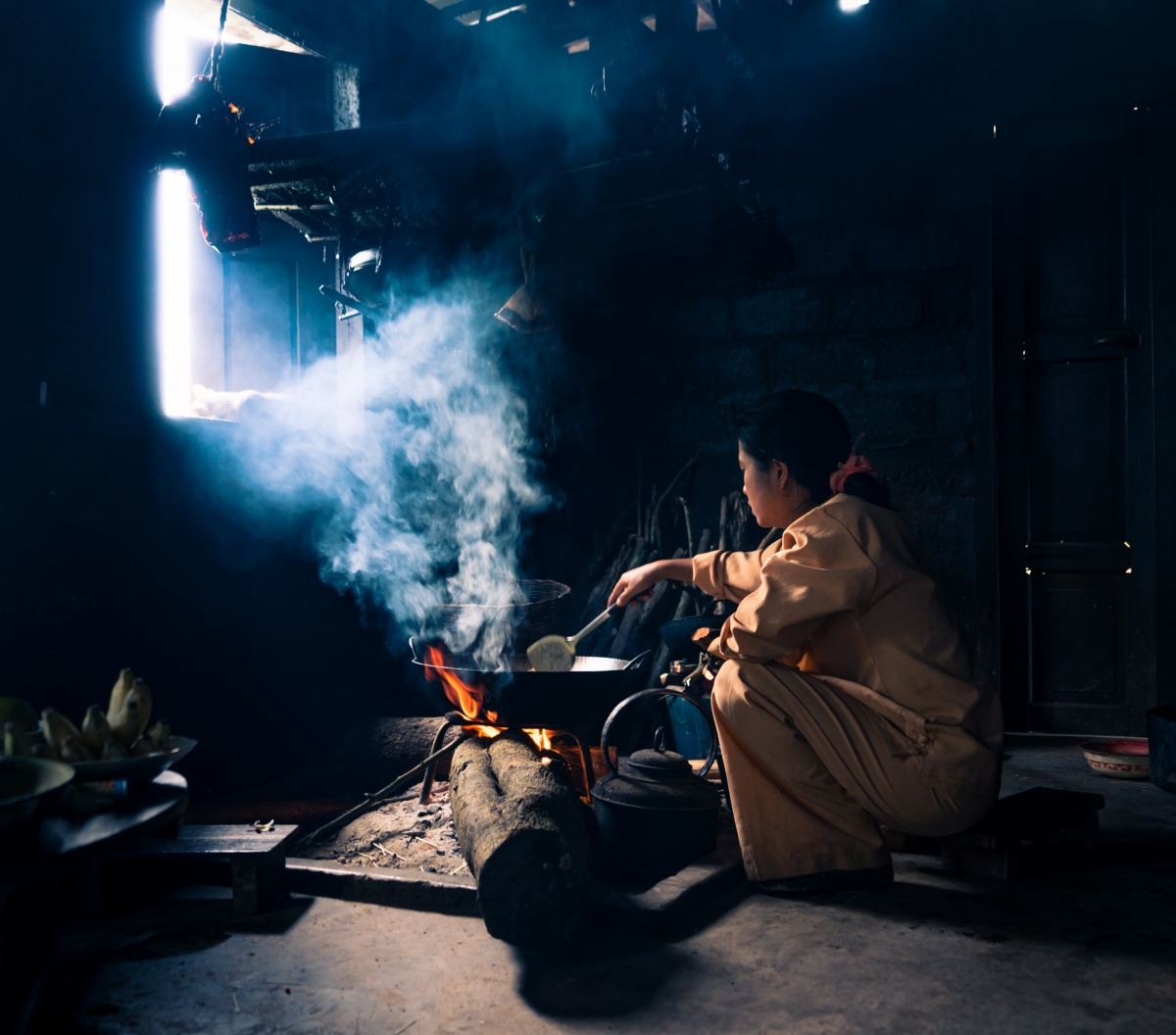 Photo of Traditional Palaung Kitchen in Kalaw, Myanmar. The kitchen is filled with smoke and a girl is cooking by open fire stove.
